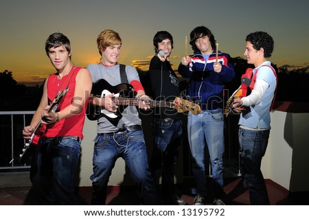 Portrait of trendy group of young musicians having fun with their instruments - stock photo