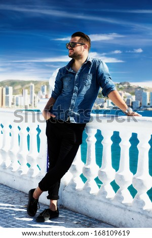 Portrait of trendy guy with beard and sunglasses on a Mediterranean beach, blurred background.   - stock photo