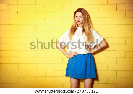Portrait of Trendy Hipster Girl Making Duck Face with Hands on Hips. Yellow Brick Wall Background with Copy Space. Urban Fashion Concept.  - stock photo