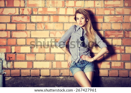 Portrait of Trendy Hipster Girl on Brick Wall Background. Urban Fashion Concept. Toned Photo with Copy Space. - stock photo