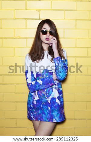 Portrait of Trendy Hipster Girl on Yellow Brick Wall Background. Urban Fashion Concept. Copy Space - stock photo