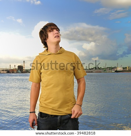 Portrait of trendy male teen looking up outdoors - stock photo
