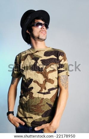 Portrait of trendy young man posing with a hat - stock photo