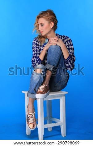 portrait of trendy young woman in elegant  dress posing on stul  - stock photo