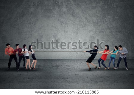 Portrait of tug of war between business people - stock photo