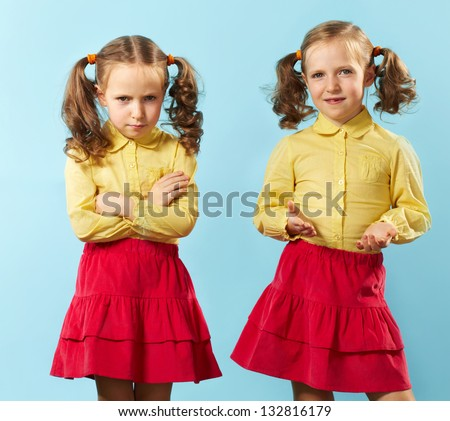 Portrait of twin girls with opposite emotions - stock photo