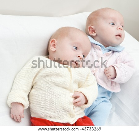 Portrait of twin sisters lying down. - stock photo