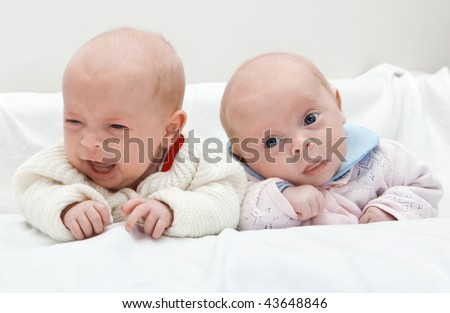 Portrait of twin sisters, one crying and one surprised. - stock photo
