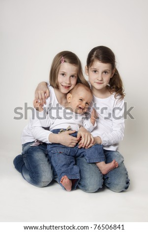 Portrait of twin sisters with baby boy brother on white background - stock photo