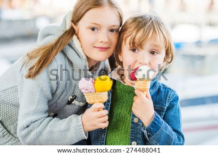 Portrait of two adorable kids eating colorful ice cream outdoors - stock photo