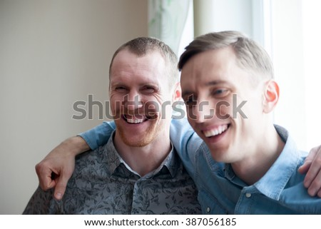 Portrait of two adult men at   window.
