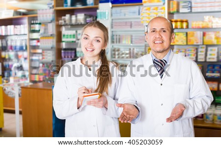 Portrait of two adult pharmacists working in modern farmacy