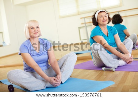 Portrait of two aged women sitting on mats in sport club  - stock photo