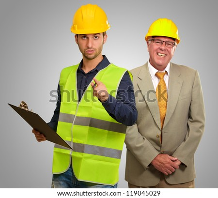 Portrait Of Two Architect Engineers On Gray Background - stock photo