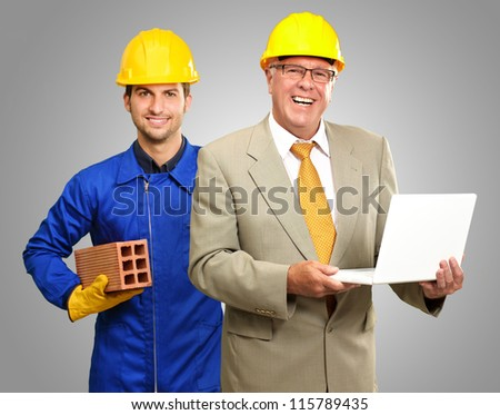Portrait Of Two Architect Engineers On Grey Background - stock photo