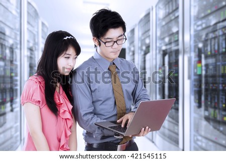 Portrait of two Asian businesspeople working with a laptop computer in the server room - stock photo