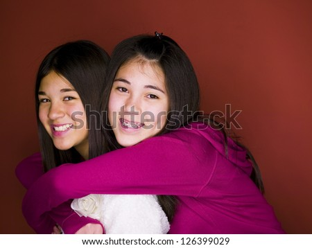 Portrait of  two Asian girls embracing - stock photo