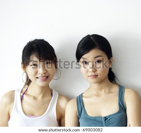 Portrait of two Asian girls leaning on wall - stock photo