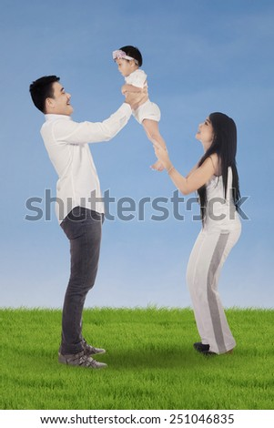 Portrait of two asian parents playing with their baby on the meadow - stock photo