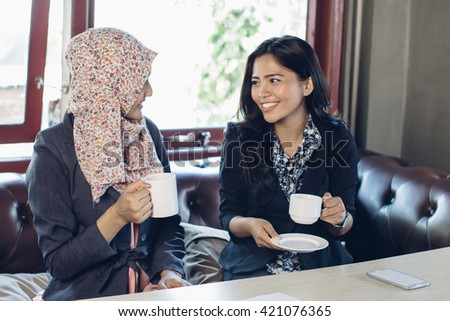 portrait of two asian woman talking while sitting on a couch enjoying coffee - stock photo