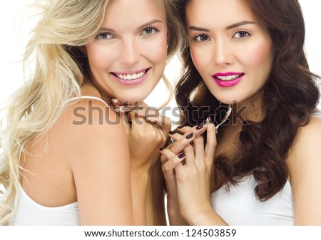 portrait of two attractive  caucasian smiling women blond  and brunette isolated on white studio shot  toothy smile face long hair head and shoulders looking at camera - stock photo