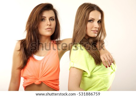 Portrait of two attractive girl friends - blond and brunette on white background