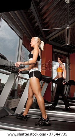 Portrait of two attractive girls doing exercise on treadmill