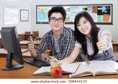 Portrait of two attractive high school student smiling at the camera while studying and showing thumbs up in the classroom - stock photo