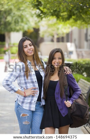 Portrait of Two Attractive Mixed Race Female Students Carrying Backpack on School Campus. - stock photo
