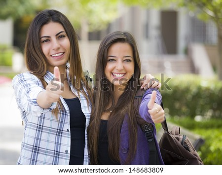 Portrait of Two Attractive Mixed Race Female Students With Thumbs Up and Carrying Backpacks on School Campus. - stock photo