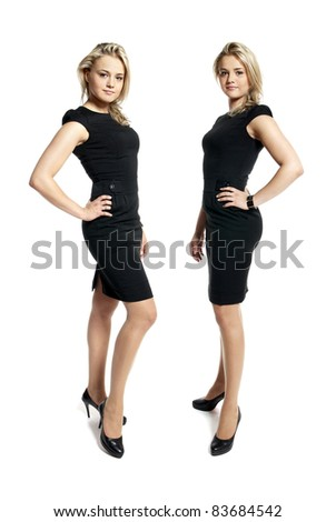 Portrait of two attractive young women in a black dress looking at camera. - stock photo