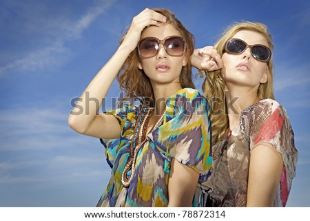 portrait of two beautiful blonde and brunette girl in sunglasses on background blue sky - stock photo