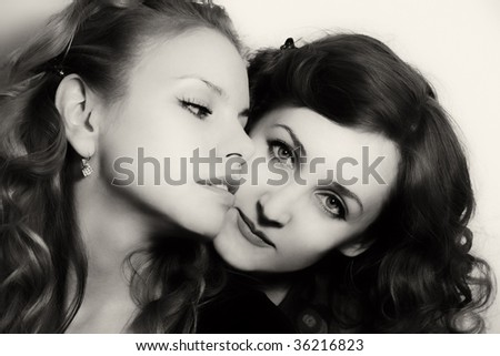Portrait of two beautiful girlfriends on a light background