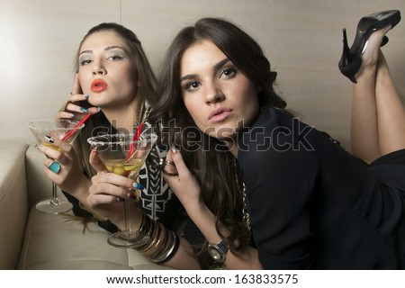 Portrait of two beautiful girls drinking martini