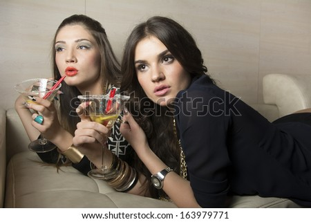 Portrait of two beautiful girls drinking martinis  - stock photo