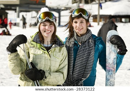 Portrait of two beautiful girls holding there skis