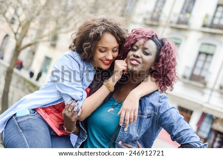 Portrait of two beautiful girls in urban background, black and mixed women. Friends talking - stock photo