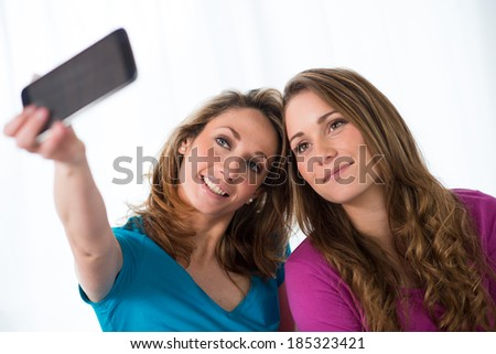 portrait of two beautiful girls making selfies at home - stock photo