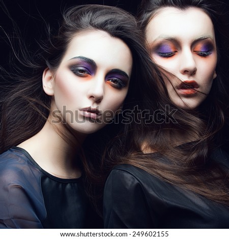 Portrait of two beautiful girls twins in the studio with bright makeup on a black background, the concept of beauty