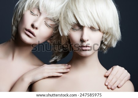 Portrait of two beautiful girls twins with closed eyes in studio - stock photo