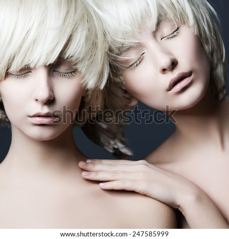 Portrait of two beautiful girls twins with closed eyes in studio, closeup - stock photo