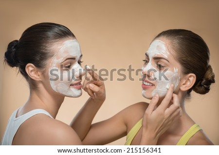 Portrait of two beautiful girls with cream on their  faces looking on each other  and touching their noses with facial cream on their fingers  isolated on beige background with copy place - stock photo