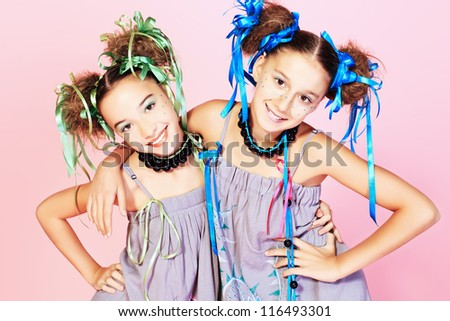 Portrait of two beautiful girls with festive make-up, hairstyle and dress. - stock photo