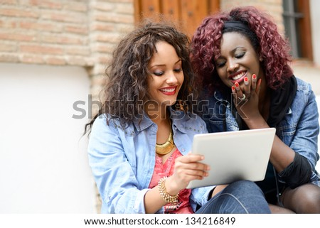 Portrait of two beautiful girls with tablet computer in urban backgrund, black and mixed women. Friends talking - stock photo