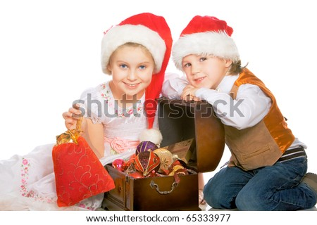 Portrait of two beautiful happy child in red caps with christmas gifts