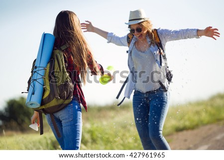 Portrait of two beautiful ladies hikers walking on the road. - stock photo