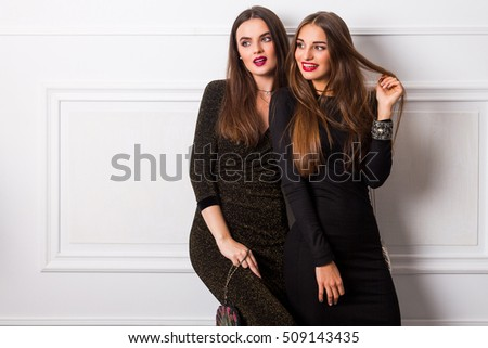 Portrait of two beautiful laughing  girls over light background. Friends wearing stylish  evening outfit long party dress.