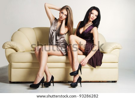 Portrait of two beautiful luxurious women sitting on a couch