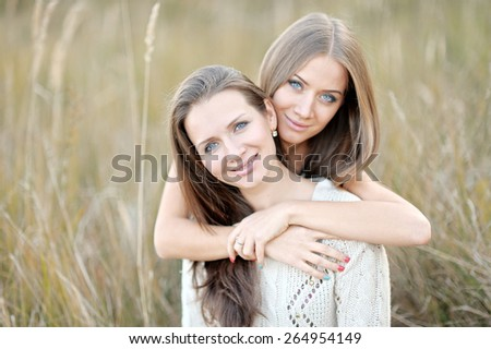 portrait of two beautiful sisters in the autumn - stock photo