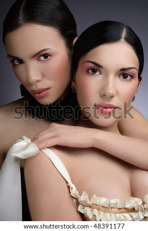 Portrait of two beautiful slim sexy young girls in corsets - stock photo